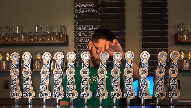 Paul Calvert, bartender at the new micro-brewery in Lansing's Old Town called Ozone's Brewhouse, pours a glass for a customer during its soft opening on Saturday, August 6, 2016.