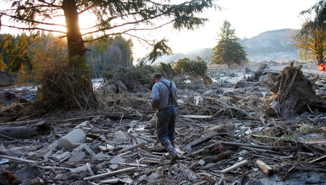 Steve Skaglund walks across the rubble on the east side of Saturday's fatal mudslide near Oso, Wash., on Sunday, March 23, 2014.