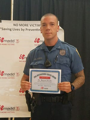 Cedar Grove Police Officer Raymond Cassella with his award from Mothers Against Drunk Driving.