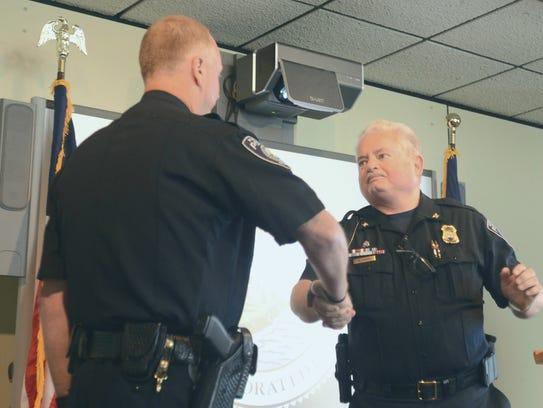 Port Huron Police Lt. Joe Platzer, left, shakes hands