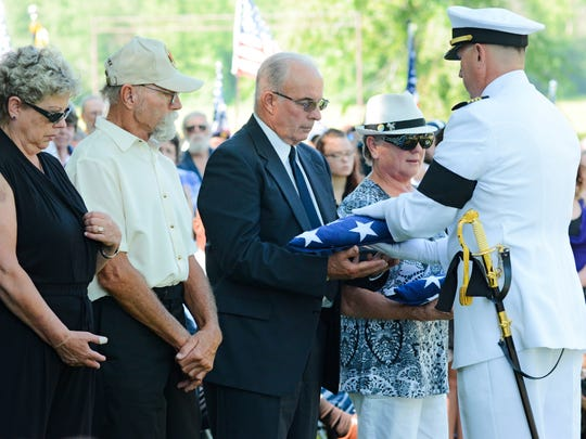 Family members receive flags in honor of Navy Fireman First Class Elmer Kerestes during his funeral in Holdingford Saturday, July 29, 2017.