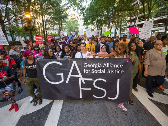 Anti-racism demonstrators participate in a rally that