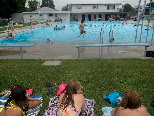 Sunbathers relax in the grass near the pool at Neiderer's in McSherrystown during the hot temperatures on Tuesday.