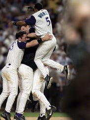 Tony Womack leaps onto his teammates after the D'Backs