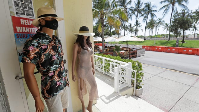 Mannequins wear masks outside a store on Ocean Drive in South Beach, Fla., where the Fourth of July holiday weekend began Saturday with some sobering COVID-19 numbers: the Sunshine Sate logged a record number of people testing positive for the coronavirus.
