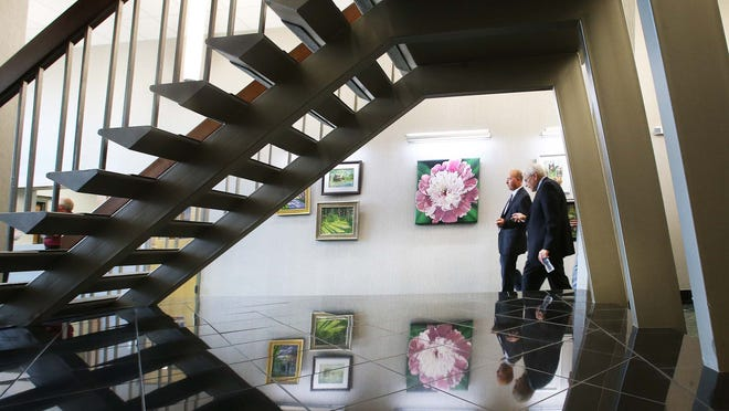 Visitors to the new city hall walk past art from the Southside Art League that hangs in the lobby. A ribbon cutting ceremony and open house officially opened the new $6-million Greenwood City Center at 308 S. Madison Avenue Thursday August 7, 2014.