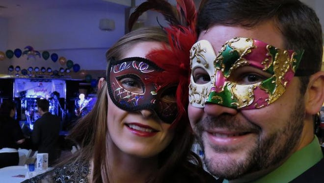 Stormie Wallace, left, and Marvin Oliver don their Mardi Gras masks for the Cordova Mall Ball Saturday night, the proceeds from which benefit the Children's Hospital at Sacred Heart.
