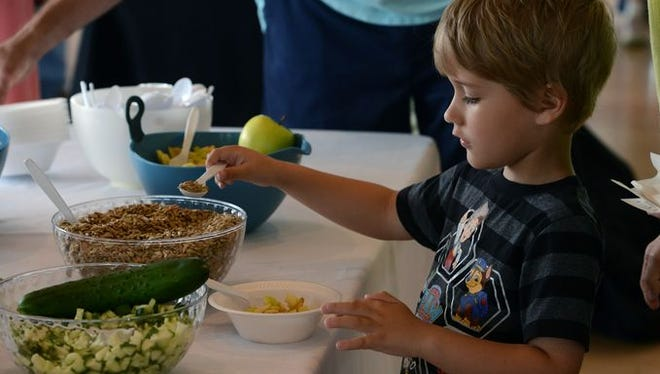 Oliver Sallis,5, makes up some chicken salad for the kids chicken salad competition Sunday during the Junior League of Pensacola's Third annual Dish It Out, at the Corrinne Jones Community Center. a tasting and shopping showcase for people who love to eat, cook and entertain.