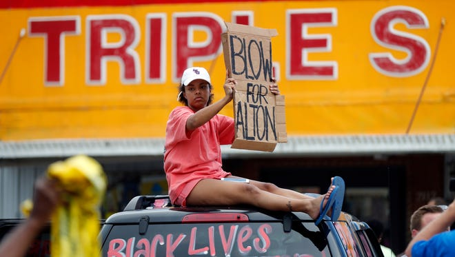 Jordan Nuerenberg holds up a sign encouraging motorists to honk outside the Triple S convenience store during a rally after Alton Sterling, a black man, was shot and killed, in Baton Rouge, La., on July 6, 2016.