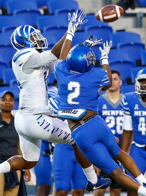 Memphis defender TJ Carter (right) knocks the ball away from receiver Antonio Gibson (left) during their spring football game at Liberty Bowl Memorial Stadium.