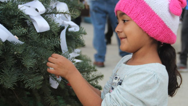 Ezra Skye Martinez, 5, places her ribbon on the ninth annual Tree of Peace in Salinas Tuesday evening.