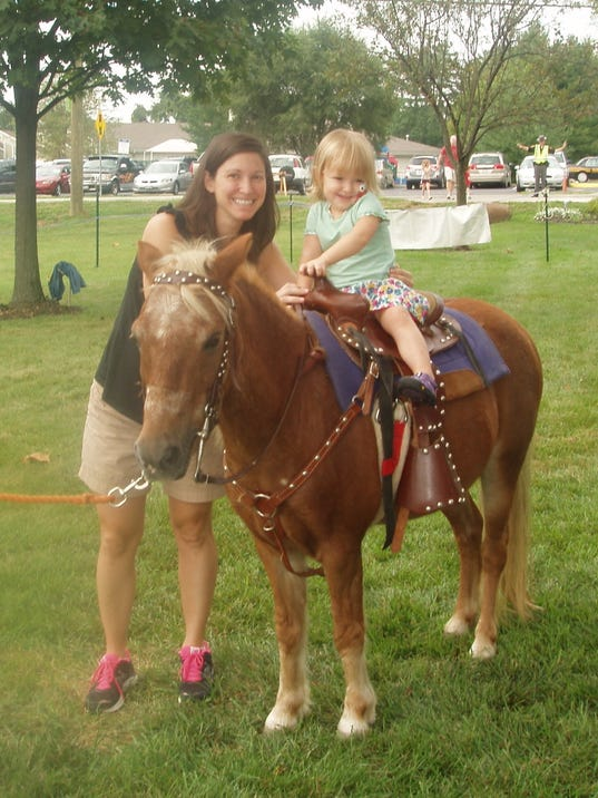 Eva Nocito Montgomery resident enjoying a pony ride with mom, Laura.jpg