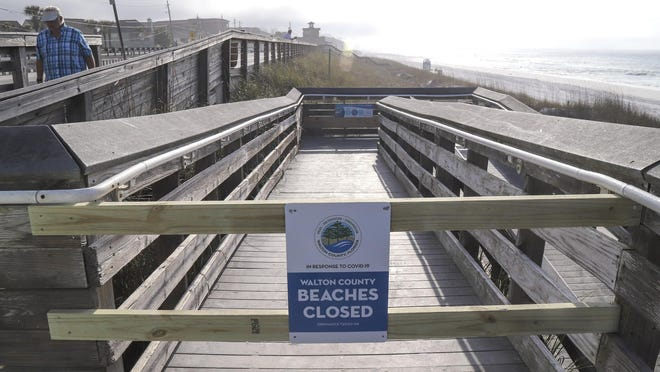 Beach access points are closed off in Walton County, Fla., Saturday, March 21, 2020.  Authorities placed beach closure orders in effect for Walton and Okaloosa Counties in the Northwest Florida panhandle due to coronavirus concerns.