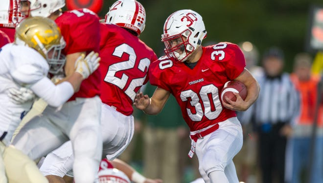 Center Grove High School junior Titus McCoy (30) rushes the ball out of the backfield during first half action of an IHSAA varsity football game Friday, Oct. 16, 2015, at Center Grove High School.