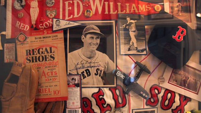 A collage of Ted Williams autographs and memorabilia hangs in the hallway of Ed Cugini's Cape Coral home.