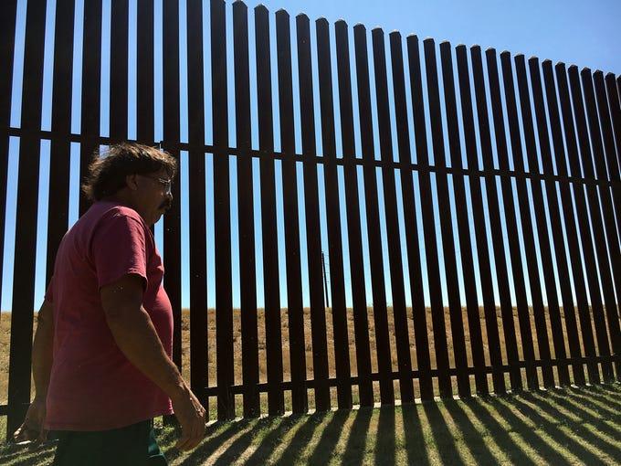 Jose Manuel Reyes walks along the border fence that