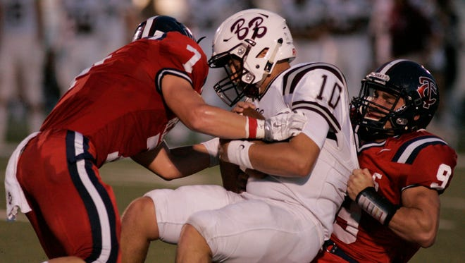 Breaux Bridge quarterback Julian Leon is tackled by the Teurlings duo Kade Sonnier (7) and Trey Menuet (9) during the Rebels' 28-14 win.