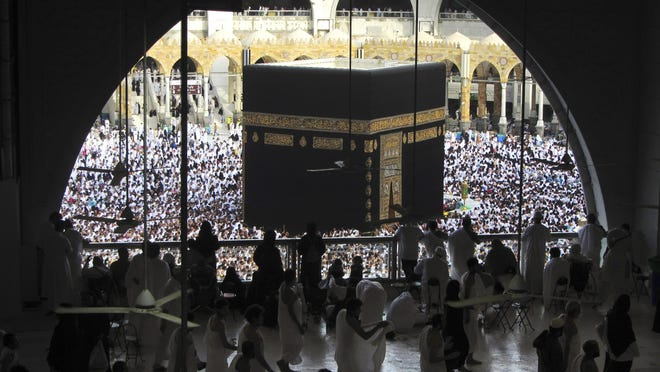 In this May 25, 2019, file photo, Muslim worshippers circumambulate the Kaaba, the cubic building at the Grand Mosque, during the minor pilgrimage in the Muslim holy city of Mecca, Saudi Arabia. Plans have been released to gradually allow Muslims back to Islam's holiest site in Mecca to perform the smaller-year-round pilgrimage, which has been suspended due to the coronavirus.