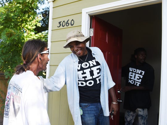 The Rev. jeff obafemi carr, middle, talks last year with Bobby Dilks, who received the first microhome built by Carr and his interfaith congregation.