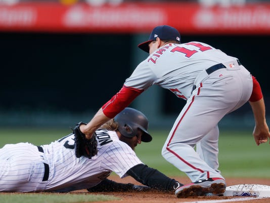 Washington Nationals first baseman Ryan Zimmerman, right, tags out Colorado Rockies' Charlie Blackmon on a pickoff throw from tarting pitcher Tanner Roark during the first inning of a baseball game Wednesday, April 26, 2017, in Denver. (AP Photo/David Zalubowski)