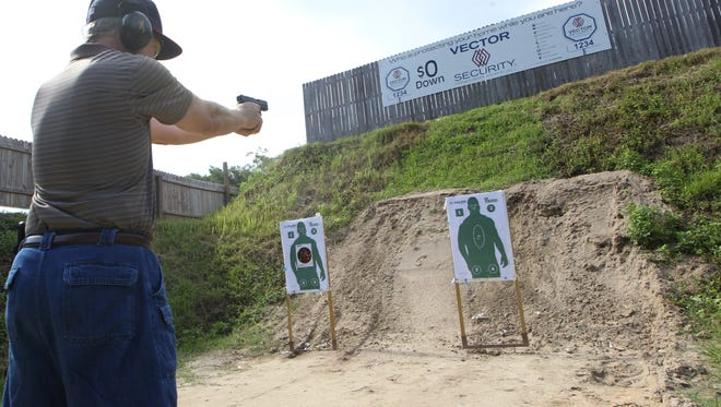 A man, who wished to remain anonymous because he believes messages on guns have been misconstrued by the media, fires a Glock .45 caliber hand gun at Talon shooting range in Midway, just outside of Tallahassee.