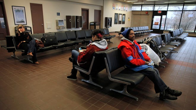 Alexander Rowland, right, waits with other passengers to board the Lake Shore Limited headed eastbound from Chicago at Rochester's Amtrak station downtown.