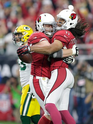 Arizona Cardinals receiver Larry Fitzgerald (11) celebrates with teammate Lyle Sendlein (63) after scoring on a touchdown reception against the Packers at University of Phoenix Stadium.