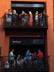 Pedestrians occupy the balconies of Honky Tonk Central