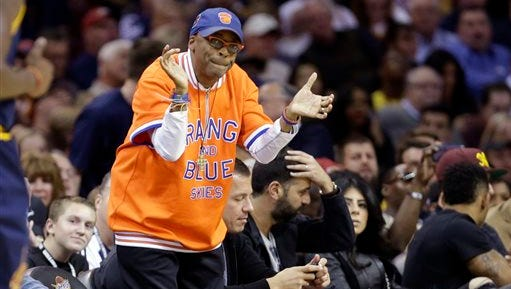 In this file photo, filmmaker Spike Lee cheers during an NBA basketball game between the New York Knicks and Cleveland Cavaliers in Cleveland.  Lee is slated to coach the Sprint NBA All-Star Celebrity Game, which will kick off festivities for the All-Star weekend on Feb. 13-15.