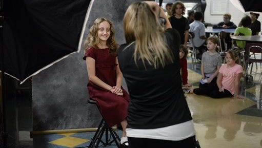 Sophia Hatcher, a fifth-grader, smiles for Pettit and Associates photographer Chelsae Hooper during picture day at Templeton Elementary School in Bloomington, Ind., Tuesday, Sept. 15, 2015.