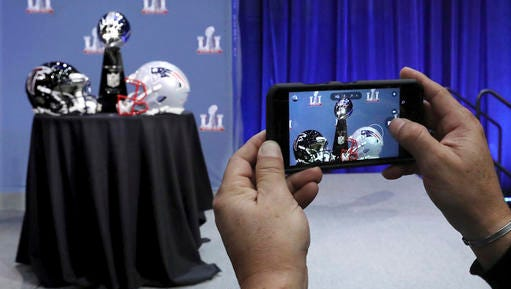 FILE - In this Wednesday, Feb. 1, 2017, file photo, an attendee snaps a photo of the Vince Lombardi Trophy and team helmets during NFL Commissioner Roger Goodell's news conference for Super Bowl 51, in Houston. The Atlanta Falcons will face the New England Patriots in the Super Bowl on Sunday. Fox will show the game online for free, but you're out of luck on phones unless you're a Verizon customer.