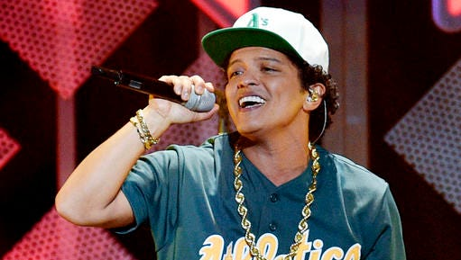 FILE - This Dec. 2, 2016 file photo shows Bruno Mars performing at the 2016 Jingle Ball in Los Angeles. Mars was in top format a  pre-Super Bowl show in Houston Friday night, Feb. 3, 2017, matching the energy he showedwhen he hit the stage at halftime last year and in 2014.