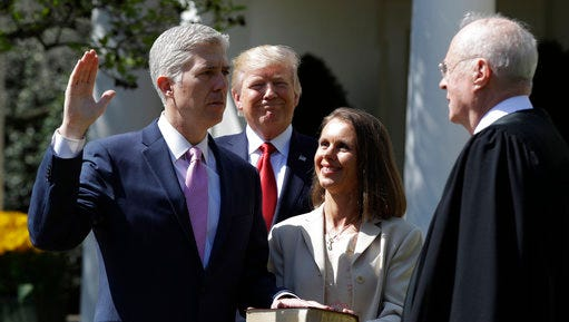 President Donald Trump watches as Supreme Court Justice Anthony Kennedy administers the judicial oath to Judge Neil Gorsuch during a re-enactment in the Rose Garden of the White House White House in Washington, Monday, April 10, 2017. Holding the bible is Gorsuch's wife Marie Louise Gorsuch.
