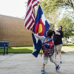 Zachary Musto, a second grader, enquires about the flags as their raised by Mariah Bouck, the head custodian, on the first day of school at Beattie Elementary School, Monday, Aug. 24, 2015, in Fort Collins, Colo.