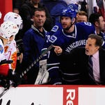 Vancouver Canucks coach John Tortorella shouts at the Calgary Flames bench after a game-opening line brawl.
