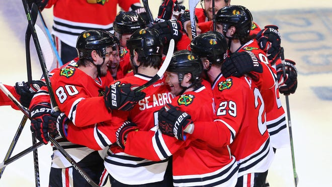 Chicago Blackhawks defenseman Brent Seabrook (7) is congratulated for scoring the winning goal during the third overtime period against the Nashville Predators in game four of the first round of the 2015 Stanley Cup Playoffs at the United Center.