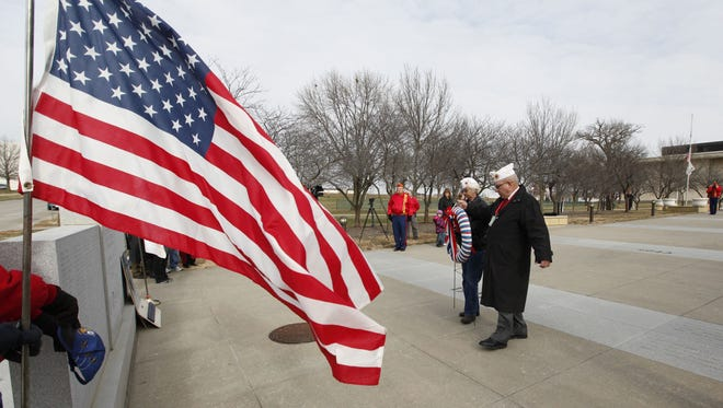 AmVets Post 2 members Janet Sprague, left, and Joe Hayes right lay a wreath during a Pearl Harbor memorial service at the Pearl Harbor Memorial near the Grimes State Office Building on Wednesday December 7, 2011.(David Purdy/The Des Moines Register)
