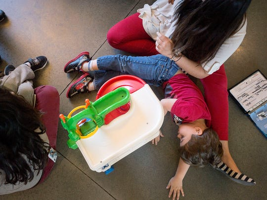 A program participant lays down while playing alongside behavioral technicians Sophia Greco, left, and Megan Burton, right, April 23, 2016 at the St. Gerard House in Hendersonville.