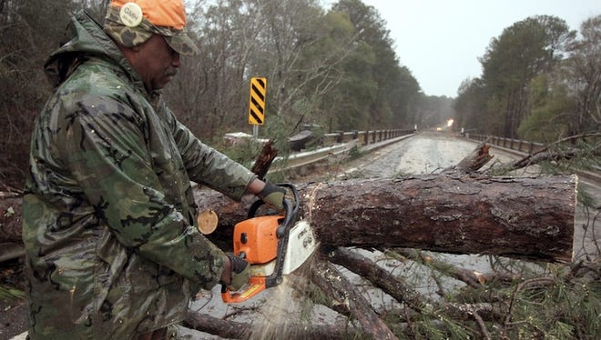 Willie J. Matthews, a Meehan, Miss., resident, cuts limbs from a fallen pine tree to remove it from a bridge on Highway 80 in Meehan near Meridian, Miss., Saturday Jan. 3, 2015, as storms blew through the area causing damage.