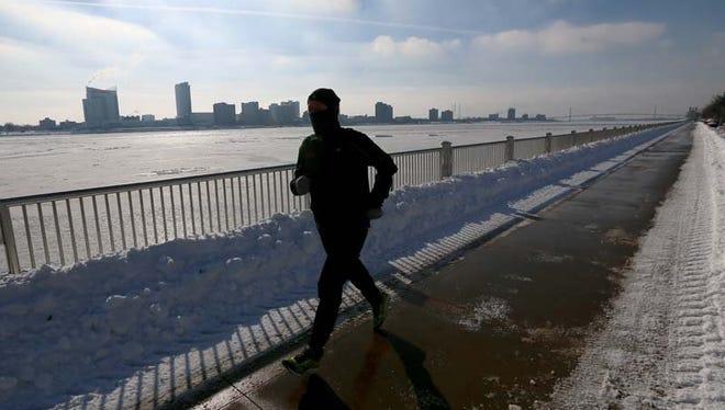 A runner jogs along the Detroit Riverfront.