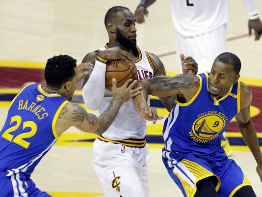 Cleveland Cavaliers forward LeBron James (23) drives between Golden State Warriors' Matt Barnes (22) and Andre Iguodala (9) during the second half of Game 3 of basketball's NBA Finals in Cleveland, Wednesday, June 7, 2017. (AP Photo/Tony Dejak)