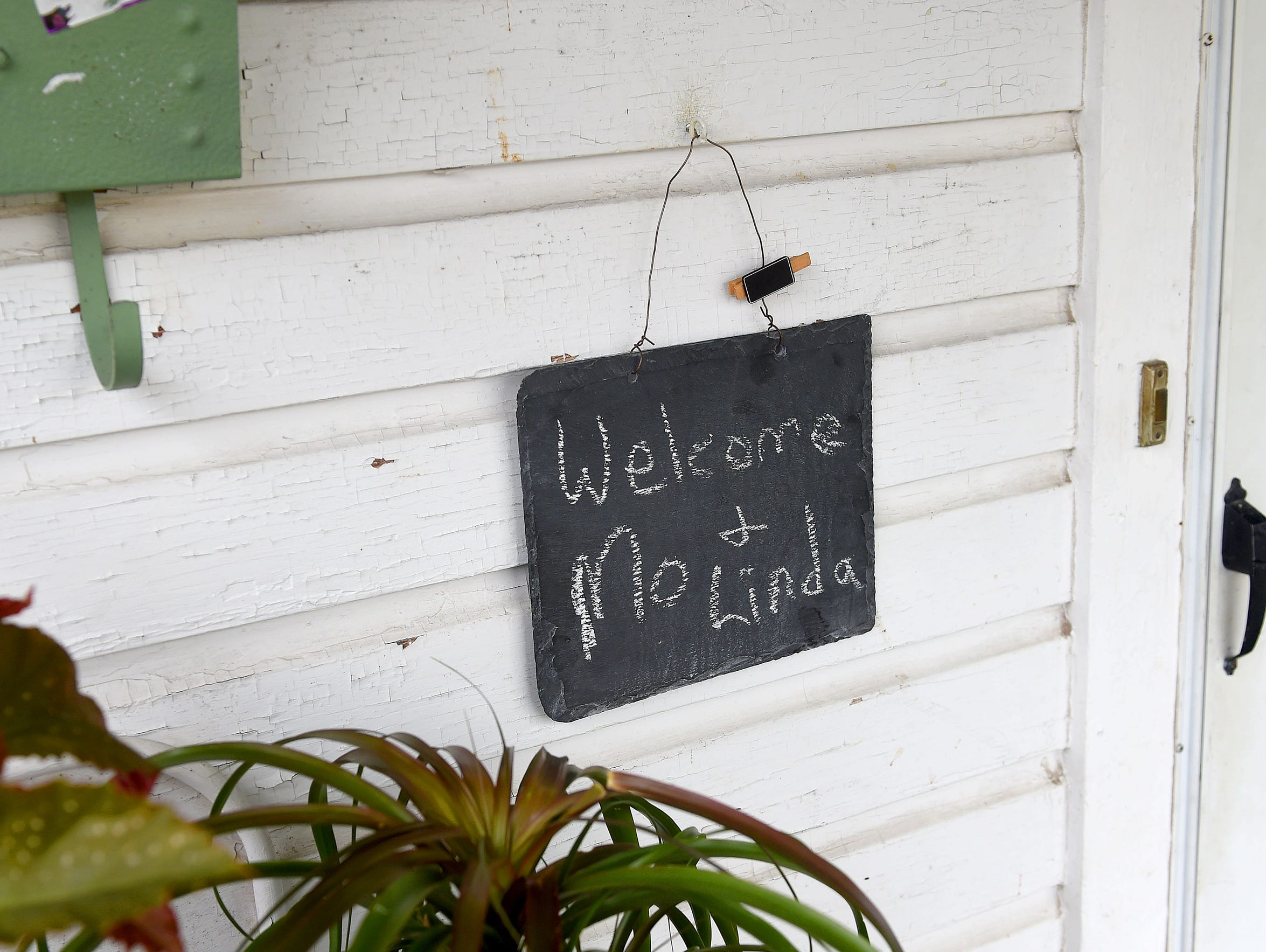 A chalkboard sign hanging next to the front door of