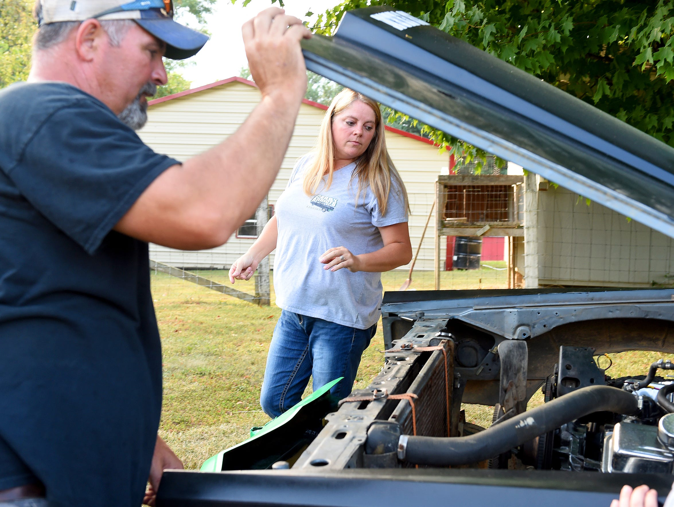 Crystal Breeden looks under the hood of one of husband