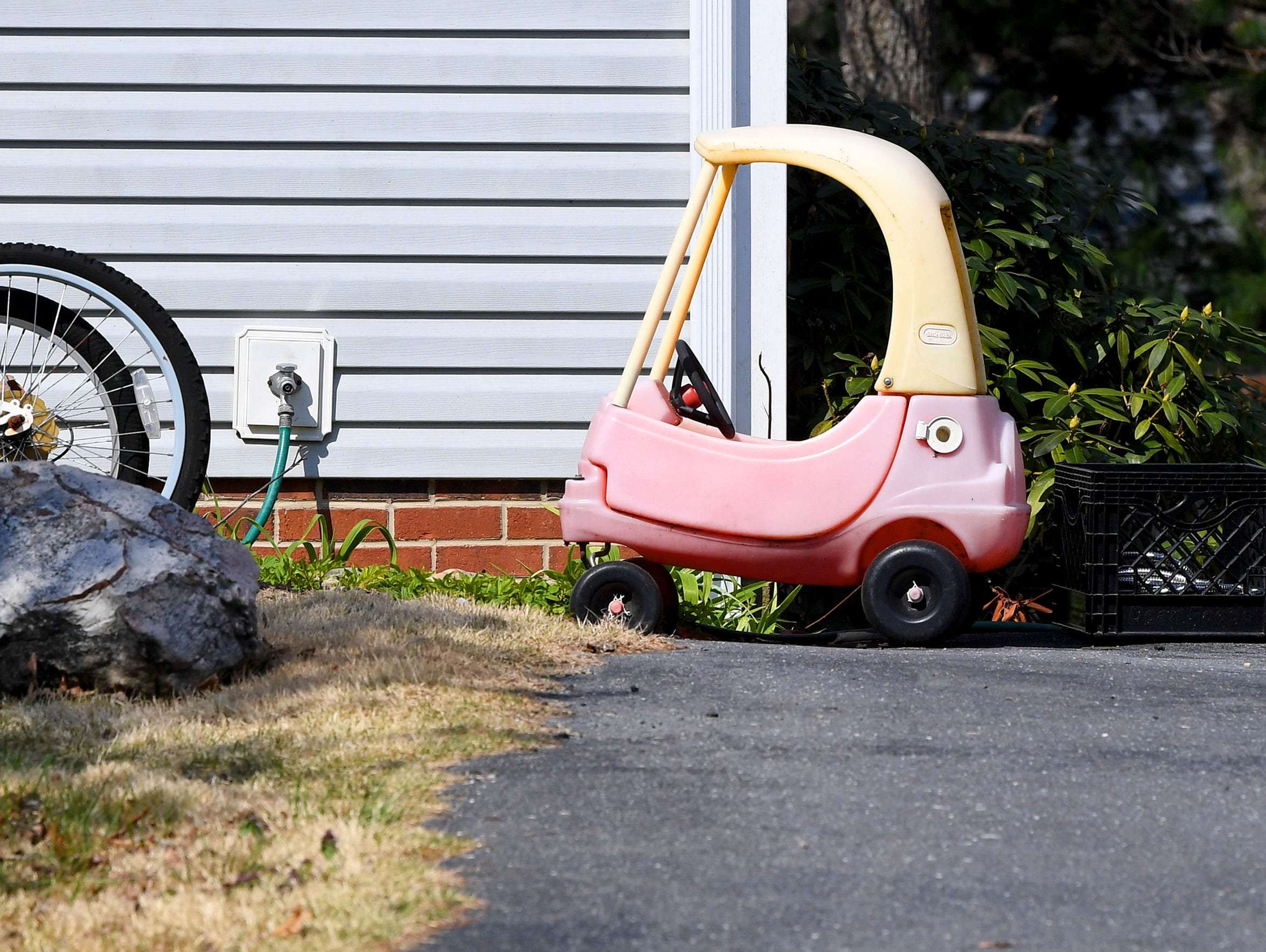 A Little Tikes Cozy Coupe Car is parked out front of