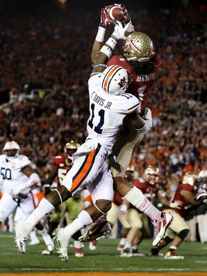 With Auburn defender Chris Davis, 11, hanging all over him, Kelvin Benjamin pulls in the game winning catch as Florida State defeats Auburn 34-31 to take the BCS National Championship game on Monday Jan., 6, 2014. The Florida State Seminoles used late game heroics to take down the Auburn Tigers at the Rose Bowl in Pasadena, CA.