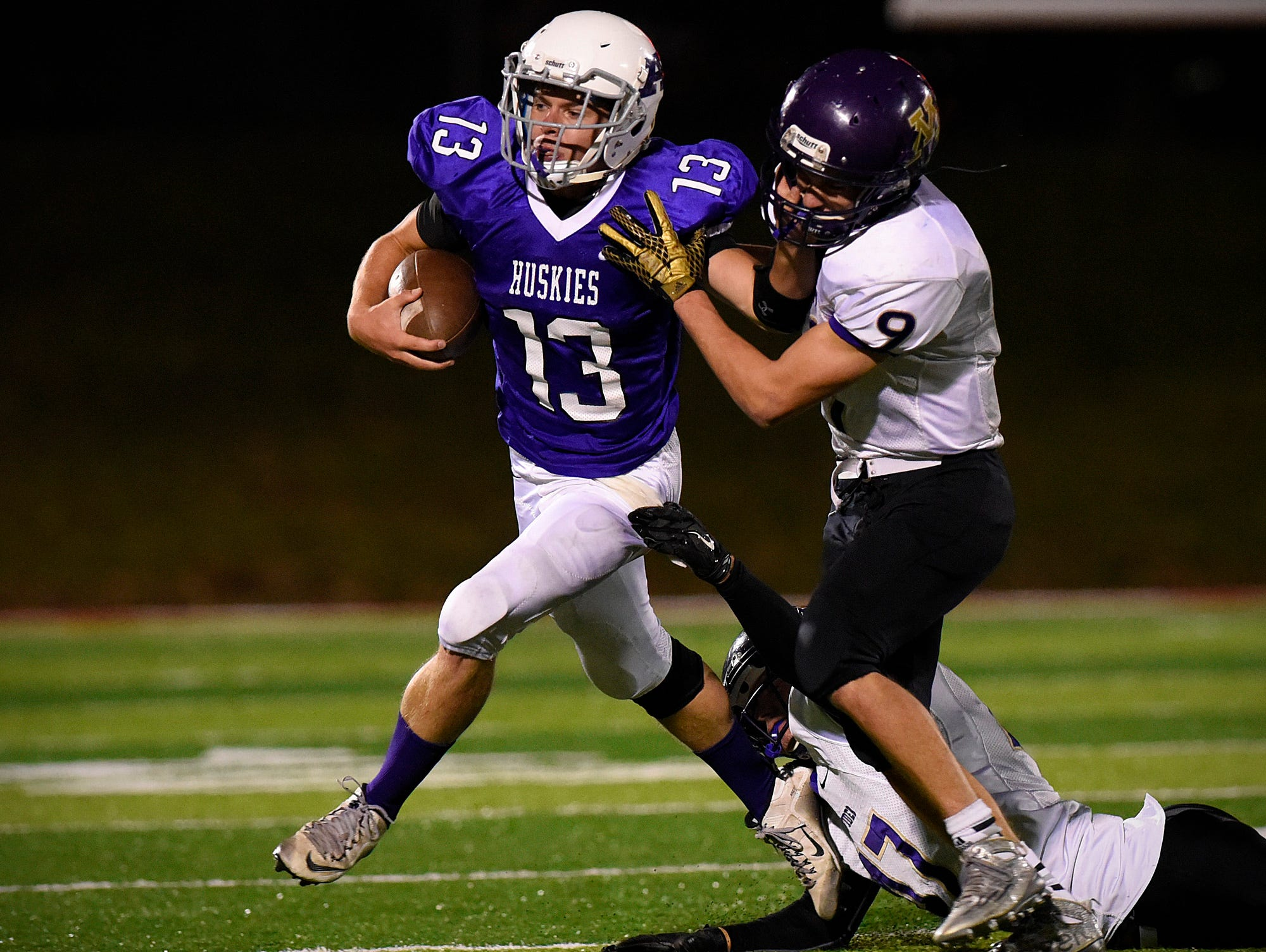 Albany's quarterback Taylor Fourre keeps the ball on a run but is brought down by Montevideo's Connor Kontz (47) and Preston Herfurth (9) after a gain during the first half Saturday, Oct. 24 at Husky Stadium.