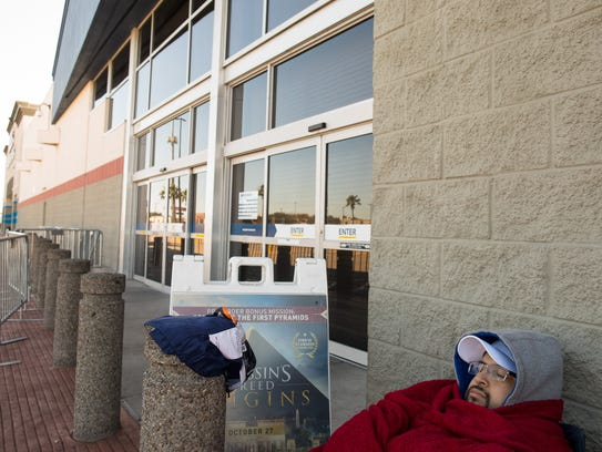 A man sleeps as he waits outside Best Buy on Thanksgiving