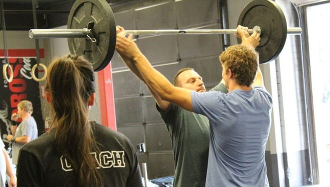 Head trainer Nick Burns helps a client improve his form during a workout at CrossFit Cedar City. Coach Taylor Whitson looks on.
