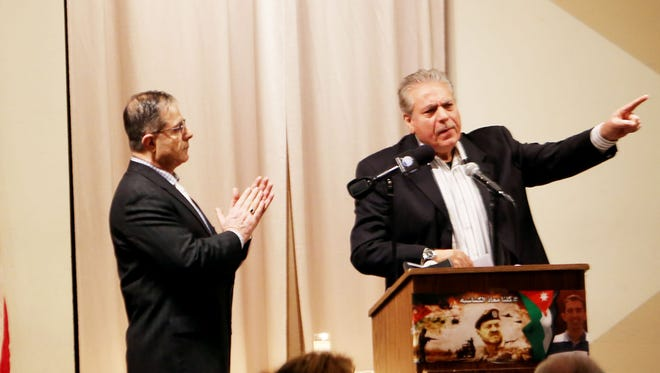 Osama  Siblani , editor-in-chief and publisher of The Arab American News, right,  speaks during a memorial service for Muath Safi Alkasasbeh, the pilot burned alive by ISIS that is presented by the Jordanian-American Community Association and the Jordan Honorary Consulate- Detroit at St. Mary's Cultural Center in Livonia Sunday, Feb. 8, 2015. William Salaita  serves as the master of ceremony listens.