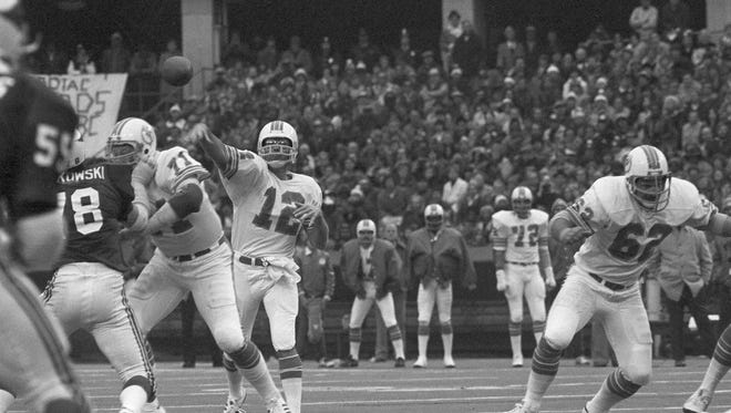 In this Nov. 24, 1977, file photo,  Miami Dolphins quarterback Bob Griese (12) passes during an NFL football game against the St. Louis Cardinals at St. Louis. The Dolphins set a Thanksgiving Day record by dropping 55 points on the Cardinals in 1977, as Griese threw for a career-high six touchdowns (AP Photo/File)